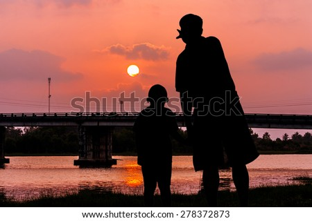 silhouette of father and son point look at the sky on the river and the  bridge sunset - stock photo