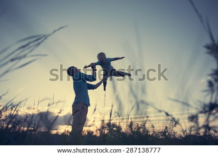 silhouette of father playing and throwing up his son in the park (intentional vintage color) - stock photo
