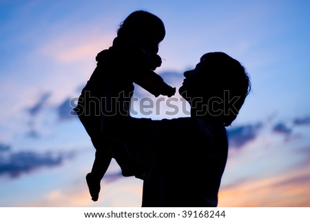 silhouette of father  toss up the son in the sky - stock photo
