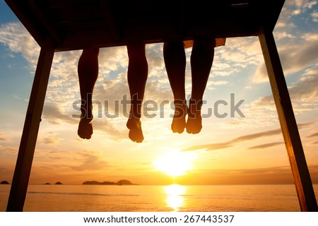 silhouette of feet of couple sitting on the pier at sunset beach, low angle view - stock photo