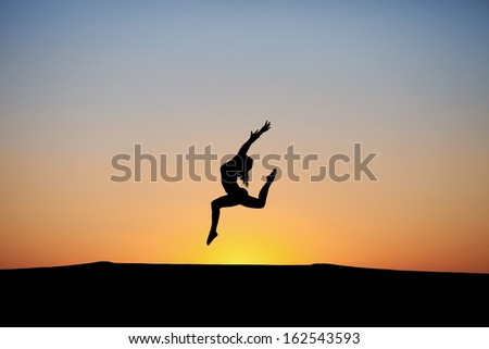 silhouette of female dancer in sunset sky  - stock photo