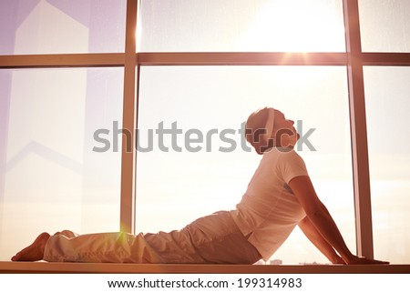 Silhouette of female doing physical exercise on background of window - stock photo