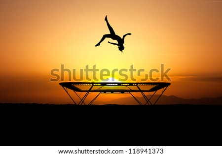 silhouette of female gymnast jumping on trampoline - stock photo