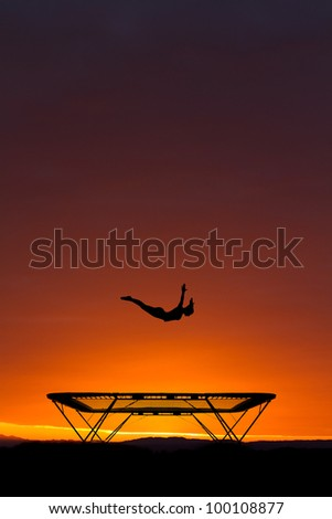 silhouette of female gymnast on trampoline in sunset - stock photo