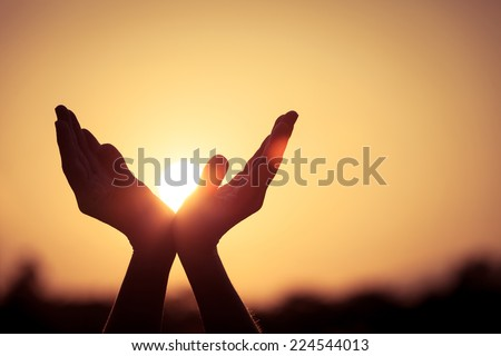 silhouette of female hands during sunset - stock photo