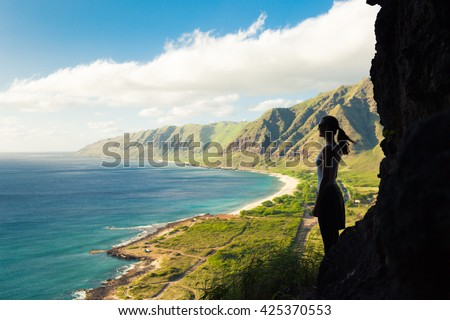 Silhouette of female hiker overlooking the beautiful coast. (location Hawaii) - stock photo