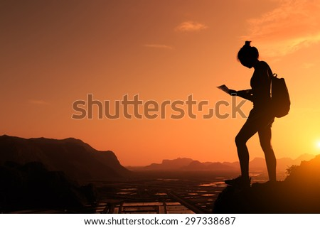 Silhouette of female hiker with backpack holding map and standing on top of a mountain during sunrise  - stock photo