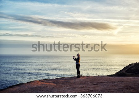 Silhouette of female taking photo of beautiful sea landscape on mobile phone camera while standing on mountain rock, young woman shoots video of an amazing scenery view of calm ocean on cell telephone - stock photo