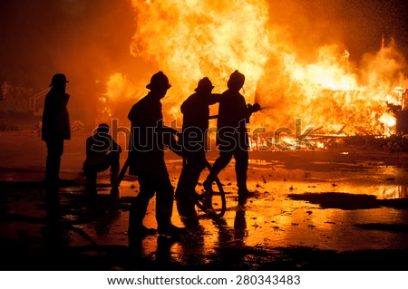Silhouette of Firemen fighting a raging fire with huge flames of burning timber - stock photo