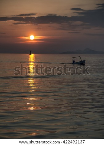 Silhouette of Fisherman at sunset returns home - stock photo
