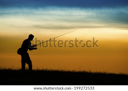 Silhouette of fisherman in sunset. - stock photo