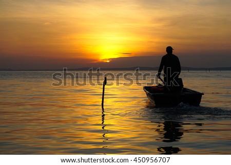 Silhouette of fisherman on boat in the sunrise at Labuan island,Malaysia. - stock photo