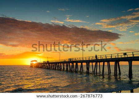Silhouette of fisherman on the jetty at sunset - stock photo