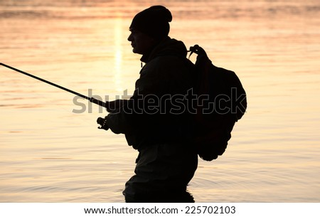 Silhouette of fishermen at sunset - stock photo