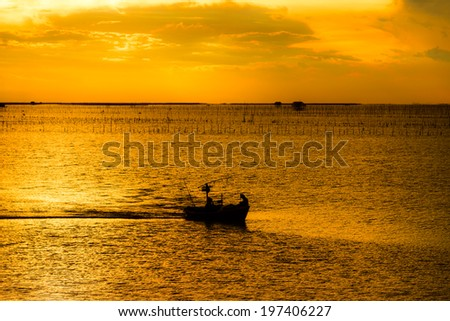 Silhouette of fishing boat and fishermen in sea at sunset background - stock photo