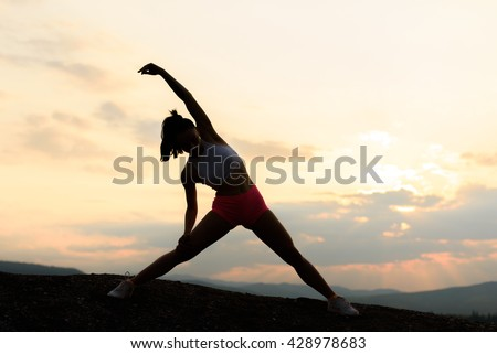 Silhouette of fitness woman exercising and stretching on beautiful summer sunset or morning at beach. Female doing relaxing yoga exercises - stock photo
