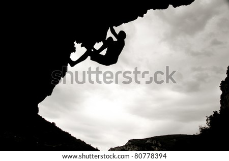 silhouette of freeclimber on overhanging rock - stock photo