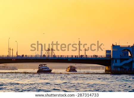 Silhouette of Galata bridge at sunset - Istanbul landmarks and seascape of the Golden Horn. Turkish passenger steamboat under the bridge, sea voyage in Turkey. - stock photo