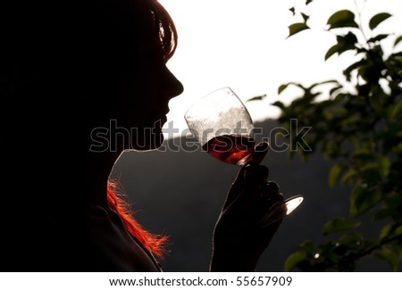 Silhouette of girl drinking wine - stock photo