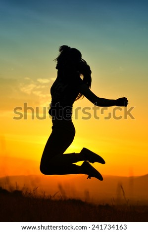 Silhouette of girl jumping in sunset - stock photo