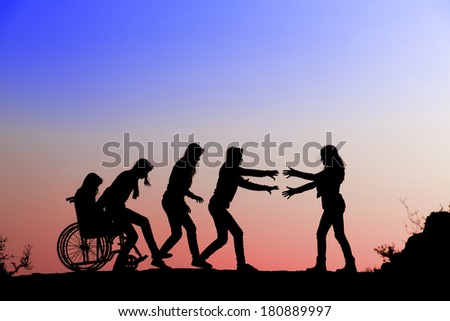 Silhouette of girl on a wheelchair and helping a friend - stock photo