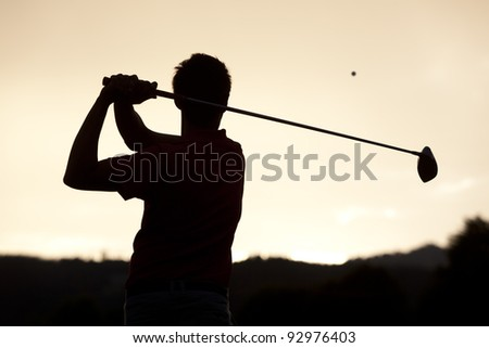 Silhouette of golf player teeing-off ball at sunset, view from behind. - stock photo