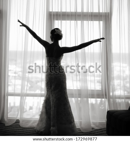 Silhouette of gorgeous bride in hotel room.  Black and white wedding picture. - stock photo