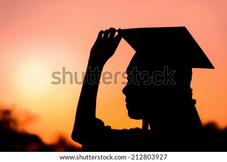 Silhouette of graduate woman in sunset - stock photo
