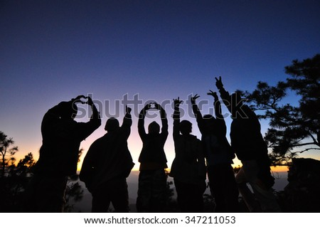 silhouette of group of friends funny in sunset - stock photo