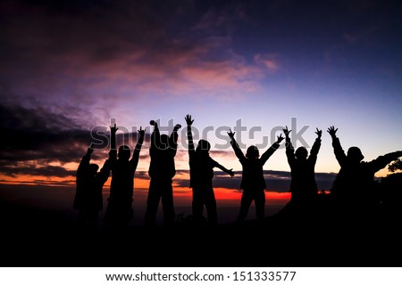 silhouette of group of friends standing in sunset - stock photo