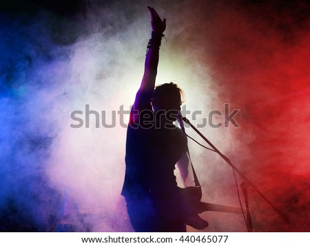Silhouette of guitar player on stage. Dark background, smoke, spotlights - stock photo