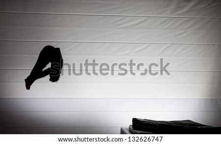 silhouette of gymnast in pike position on trampoline - stock photo