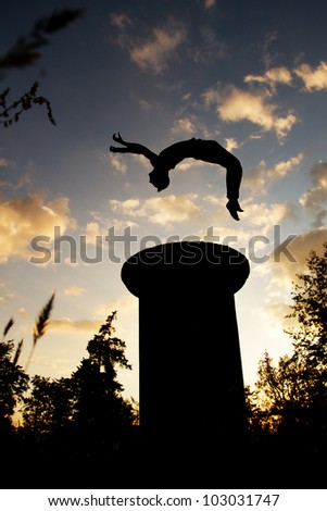 silhouette of gymnast jumping in sunset on tower - stock photo