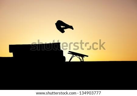 silhouette of gymnast on mini trampoline - stock photo