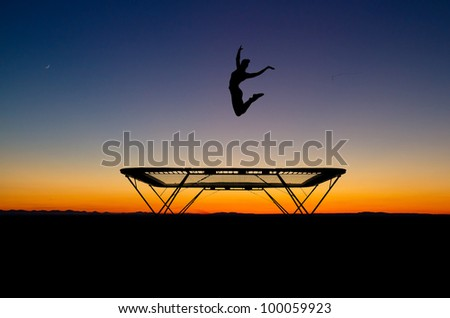 silhouette of gymnast on trampoline in sunset - stock photo