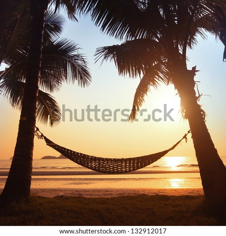 silhouette of hammock and palm trees on the beach - stock photo