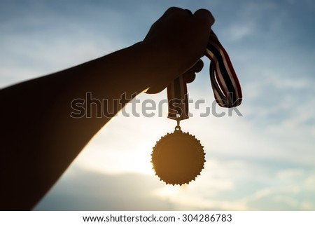 Silhouette of Hand holding gold medal on sky background . concept of victory - stock photo