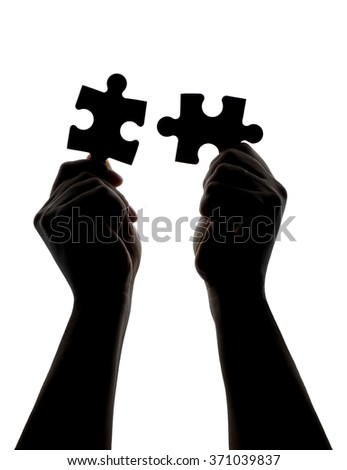 Silhouette of hands trying to connect two pieces of a puzzle isolated - stock photo