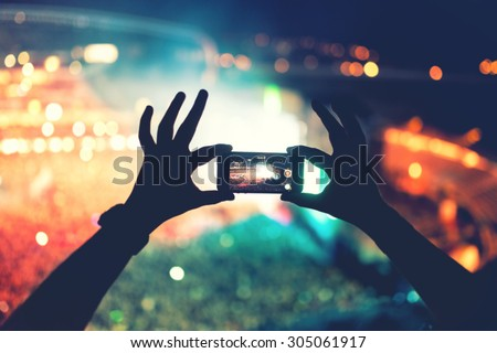 Silhouette of hands using camera phone to take pictures and videos at pop concert, festival. Soft effect on photo - stock photo