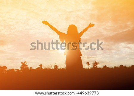 silhouette of happiness woman stays outdoor with sky background,cheering woman hiker open arms - stock photo
