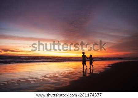 Silhouette of happy children playing on the beach while holding hands at sunset time - stock photo