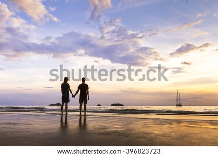 Silhouette of happy couple having a romantic coastal walk and near the sea in paradise island - stock photo