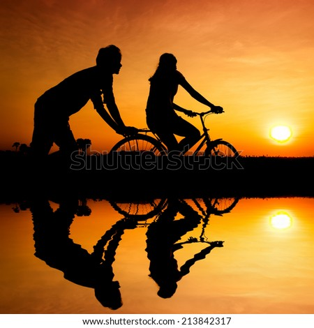 silhouette of happy couple  with water reflection  - stock photo