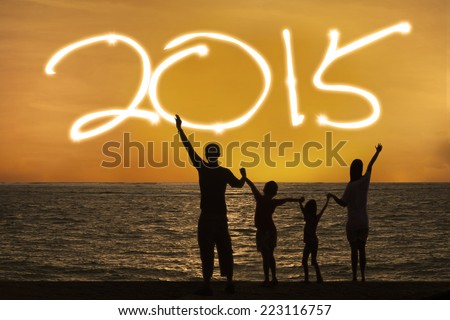 Silhouette of happy family on beach with number 2015 on the sky - stock photo