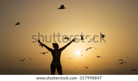 silhouette of happy girl on the beach with orange sunset and sun with seagulls - stock photo