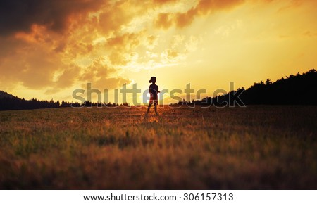 Silhouette of happy kid playing on meadow at sunset - stock photo