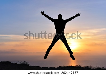 silhouette of happy man on the sunset on mountain rock above the sea - stock photo