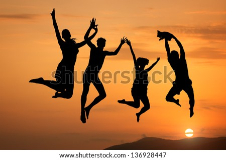 Silhouette of happy people jumping at sunset and sea - stock photo