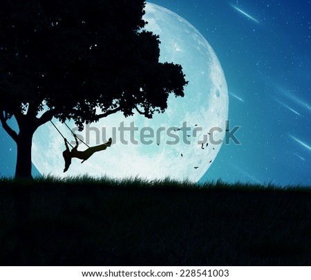 Silhouette of happy young woman on a swing of a tree isolated on beautiful background of moon, earth, night skyline, falling stars. Body vitality, human spirit well being, freedom, happiness concept - stock photo