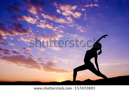 Silhouette of healthy woman doing yoga meditation during sunrise with natural sunlight outdoor. - stock photo